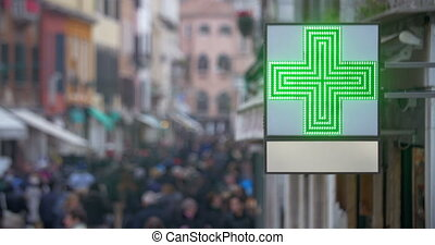 Pharmacy sign with green cross in busy street - Outdoor...