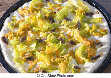 raw pizza with zucchini flowers and anchovies reedy to be...