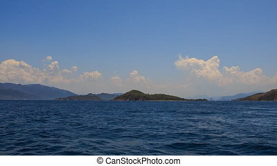 view of azure sea against clouds sky and mountains at...