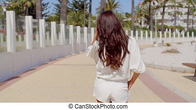 Woman Looking Back and Walking on Beach Promenade - Rear...