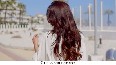 Brunette Woman in Sunglasses on Beachfront Walk
