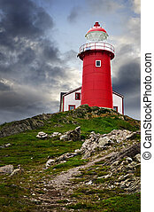 Lighthouse on hill - Red lighthouse on hill against stormy...
