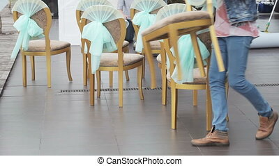 Chairs at wedding ceremony - Man in jeans arranges chairs...