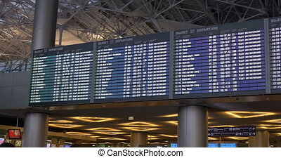 Digital flight schedule at the airport - Panning shot of...