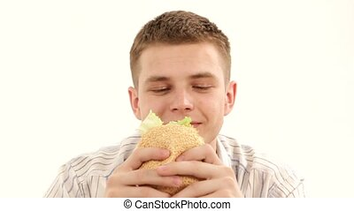 Eat A Sandwich - Young man eating a delicious sandwich with...