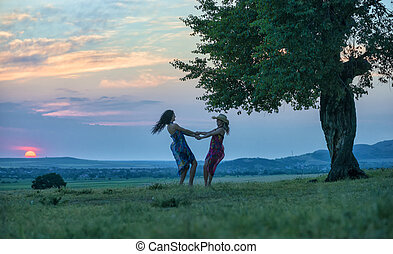 two women dancing on the grass at sunset time