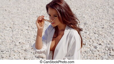 Brunette Woman Adjusting Sunglasses on Stone Beach -...
