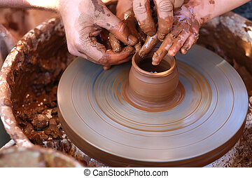 Hands working on pottery wheel - Potter's hands guiding...