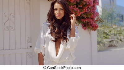 Brunette Woman Standing Outdoors with Hand in Hair -...