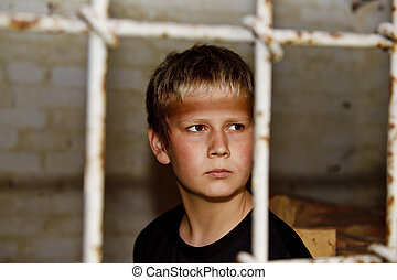 Sad looking boy behind bars - Portrait of young boy looking...