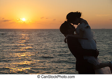 Couple standing by the sea. Romantic sun sets. The sky began...