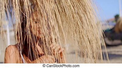 Woman Standing Underneath Grass Beach Umbrella - Head and...