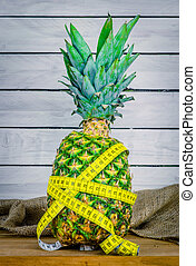 Pineapple with measure tape on a table