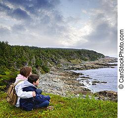 Children sitting at Atlantic coast in Newfoundland -...