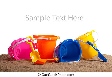 Assorted colored buckets on sand with copy space - Assorted...