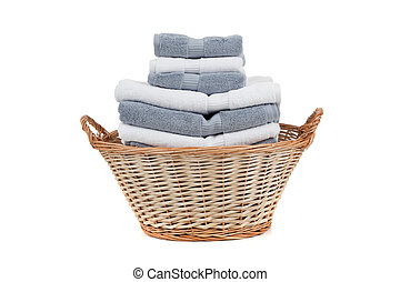 Wicker laundry basket full of white and gray towels - A...