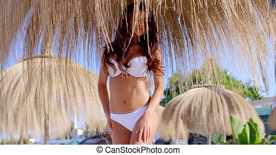 Woman in Bikini Standing Under Beach Umbrella - Brunette...