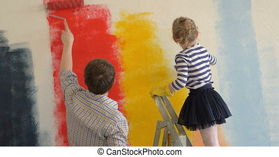 Father and daughter painting walls in bright colors - Father...