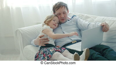 Father and daughter using laptop on the sofa - Father and...