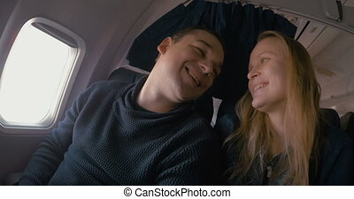 Young loving couple in the plane - Young man and woman...