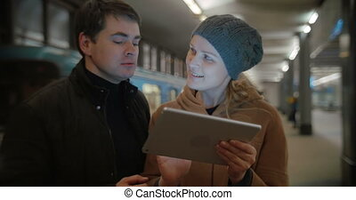 Young people discussing something using pad at metro station...