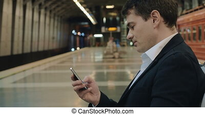 Young handsome businessman texting on cell in subway