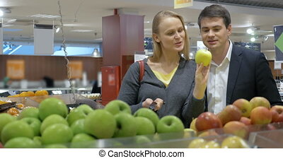 Happy young couple buying apples in the supermarket