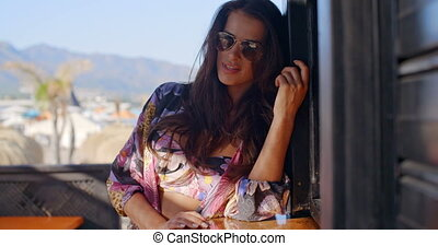 Woman Wearing Sunglasses on Tropical Balcony - Waist Up...