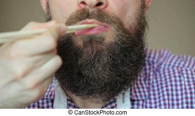 Bearded man eating sushi