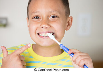 Boy brushing teeth and braces. - Young boy brushing pointing...