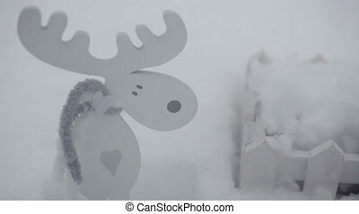 wooden toy moose and a small fence in the snow