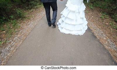 Wedding couple walking in a field under the blue sky