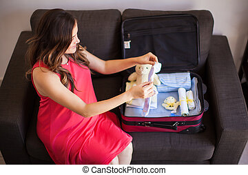 Pregnant woman packing a suitcase