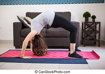 Pregnant woman doing a backbend - Young pregnant brunette...
