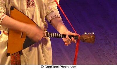 Playing on the balalaika