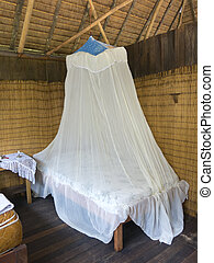 Mosquito net - Bedroom in a wood bungalow. Vertical shot.