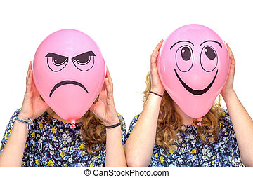 Two girls holding pink balloons with facial expressions of...