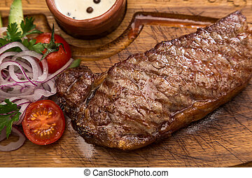 roast meat steak with vegetable garnish and sauce