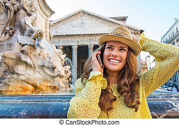 Happy woman chatting on mobile phone at Pantheon fountain -...