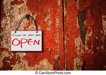 come in we are open hanging sign isolated on wall for adv or...