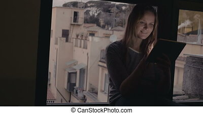 Woman using tablet PC sitting on windowsill - Dolly shot of...