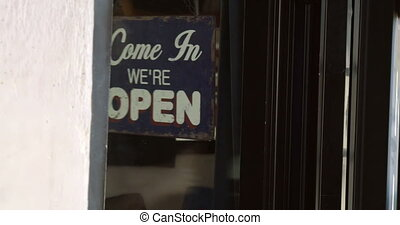 Closing the door and changing shop-sign - Dolly shot of...