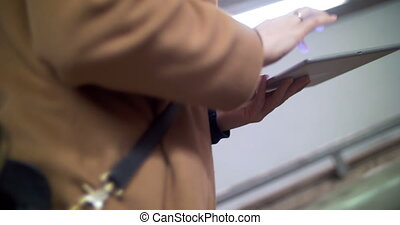Woman with pad going upstairs in subway - Woman in coat...