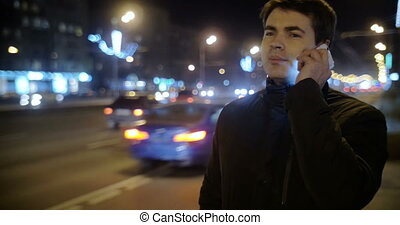 Man having a phone talk by the road at night