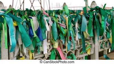 Traditional green ribbons on the fence of muslim tomb on...