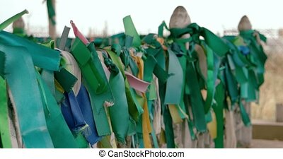 Green ribbons on a fence of ancient muslim tomb fly in the...