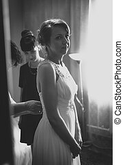 Black and white photo of bridesmaid helping bride to put on...