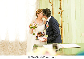 happy bride and groom kissing first time at registry office...