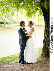 bride with long hugging with groom under big tree at park -...
