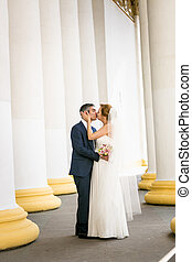 newly married couple kissing at old white columns -...